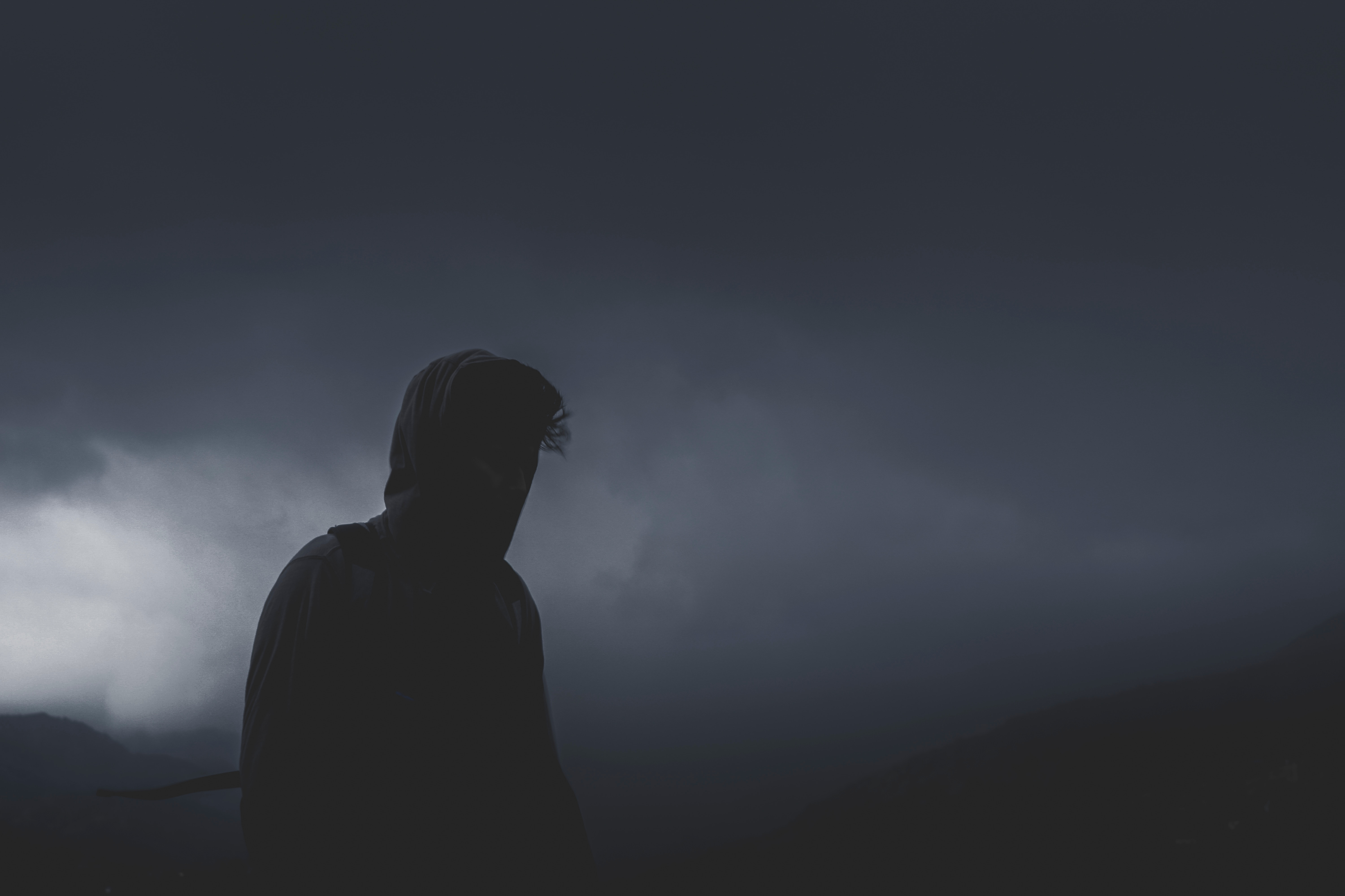The dark silhouette of a man walking alone in the mountains on a dark, cloudy night