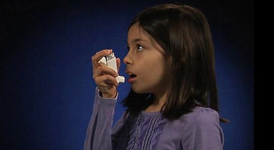 A young girl using an inhaler
