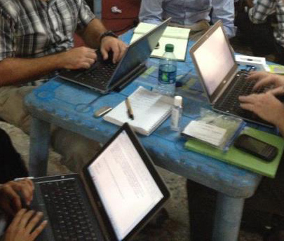 Four people using laptops while seated around a small table cluttered with notebooks, pens, cell phones, and a water bottle.