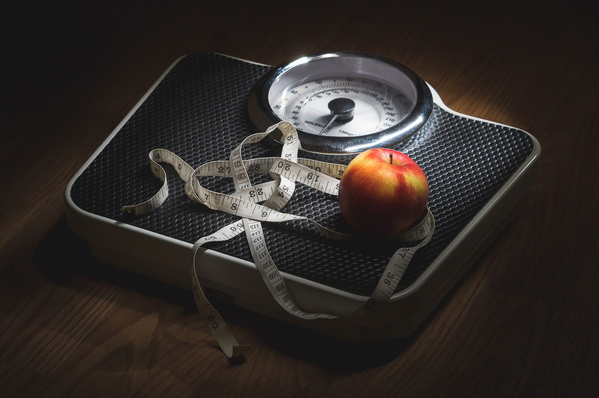 An analog bathroom scale with a measuring tape and an apple placed on top