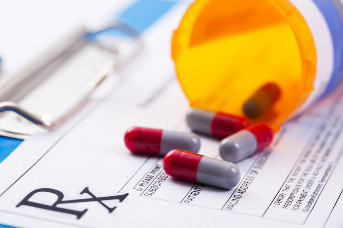 An open prescription bottle on its side with one pill capsule in the bottle and 4 outside of the bottle on top of a prescription form clipped to a clipboard