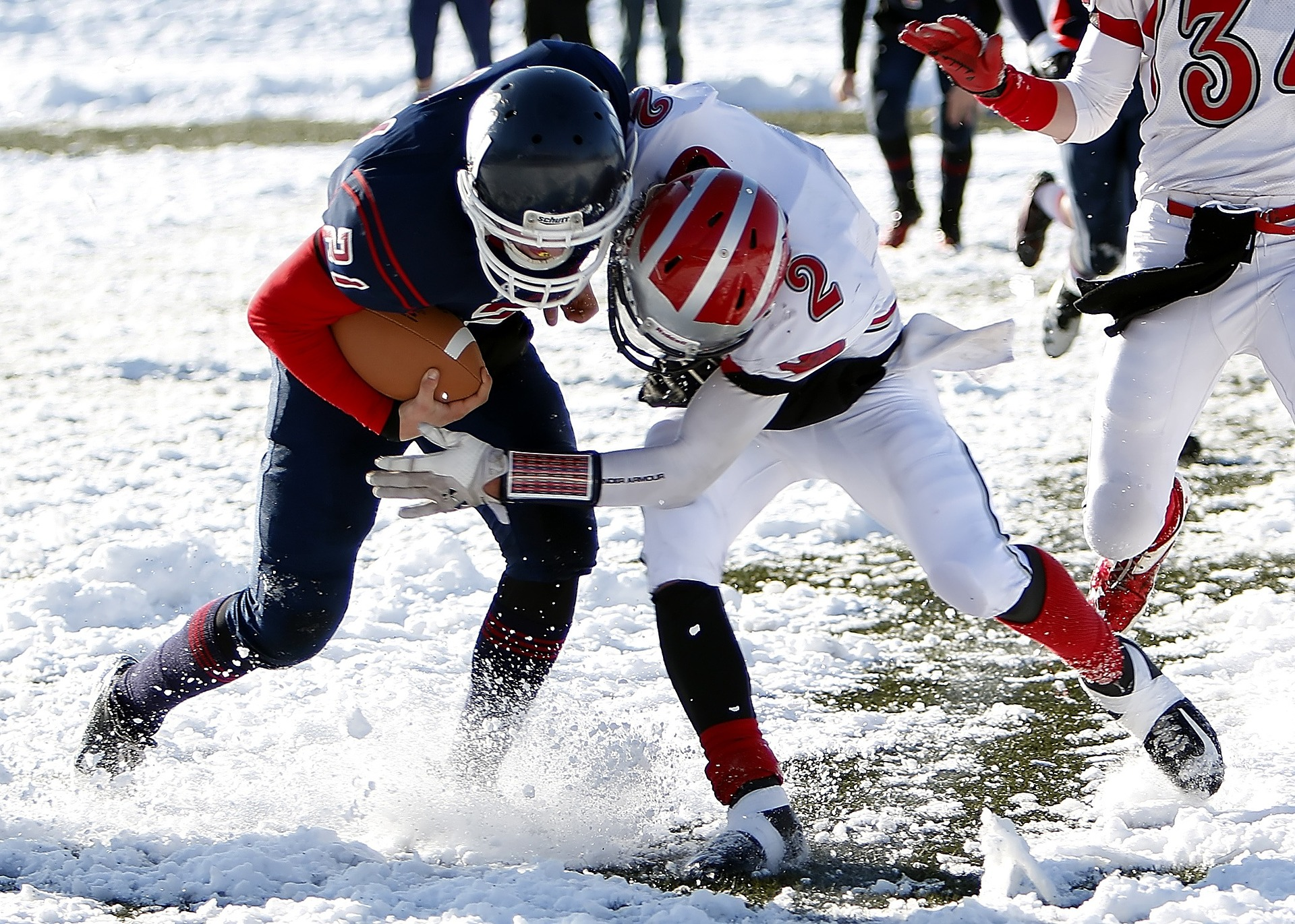 On a snowy field, one football player in a dark blue uniform, is holding a football as another football player from the opposing team in a white uniform, tackles the player with the football and their helmets collide
