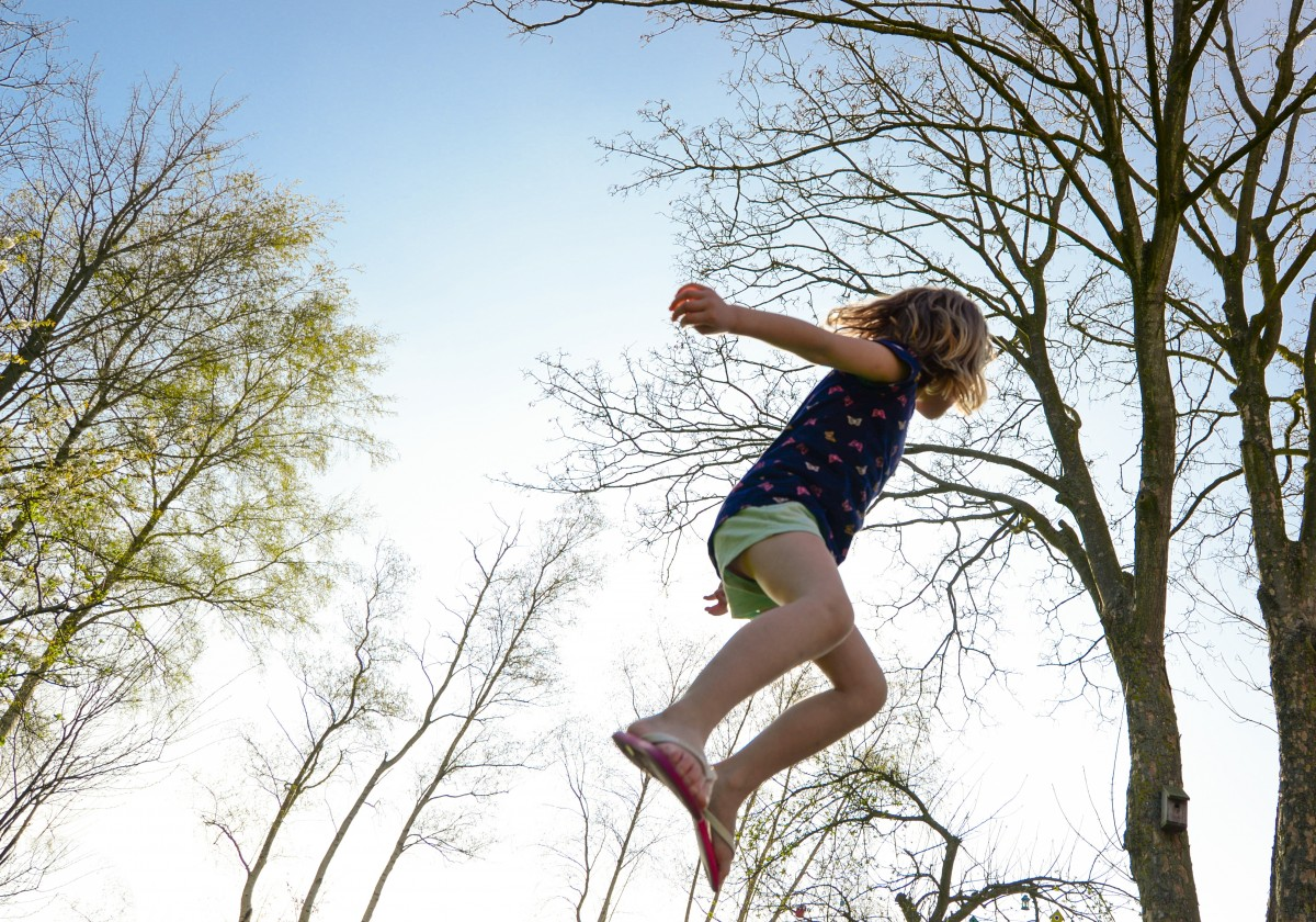 A young girl jumping in the air amidst trees bare of leaves and clear skies