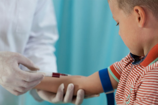 A child having blood drawn by a lab technician