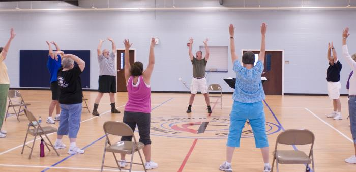 A senior fitness class taking place in a gymnasium with the participants in a circle, each standing in front of a folding chair, stretching with arms lifted up high