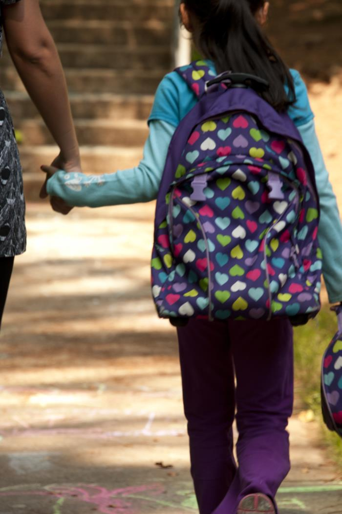 View from behind of an elementary school-aged girl, wearing purple pants, a light blue shirt and a backpack, walking on a sidewalk holding hands with an adult woman