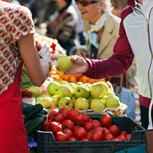 People are selecting fresh fruit and vegetables from a produce market while one customer is paying the vendor for a green apple.