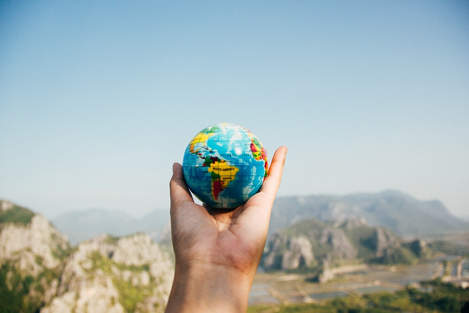 A hand holding a small globe with a mountain landscape in the background