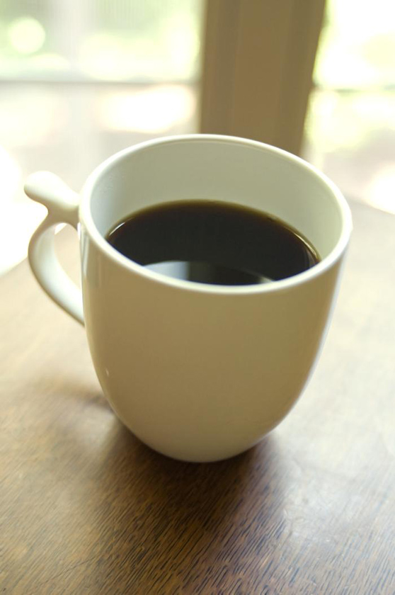 A cup of coffee in a white mug on a wooden table near a window.
