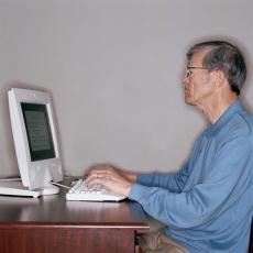 Photograph of a senior man using a computer