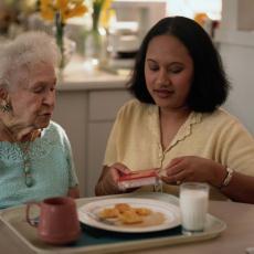 Fotografía de una mujer mayor almorzando con la asistencia de su cuidadora