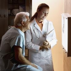 Fotografía de un paciente y una doctora mirando una radiografía