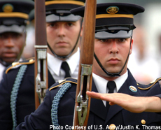 Photograph of a U.S. Army Drill Team executing precision drill movements during a festival