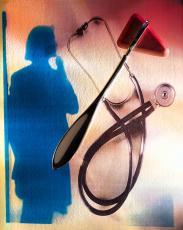 Fotografía de un estetoscopio y un martillo de reflejos con el perfil de una mujer en segundo plano