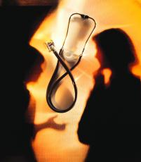 Photograph of a stethoscope with the shadows of two women in the background