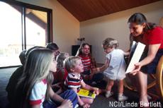 Fotografía de una mujer leyéndoles a unos niños