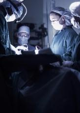 Photograph of male and female doctors performing surgery