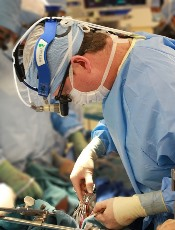 Photograph of a male surgeon performing surgery