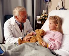 Photograph of a male doctor with his stethoscope on the teddy bear of a young female patient