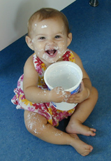 A photograph of a toddler eating yogurt