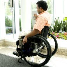 Hombre en una silla de ruedas saliendo de un edificio