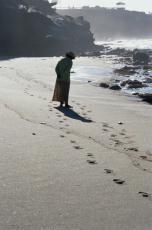 Fotografía de una mujer caminando por la orilla del mar