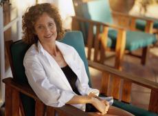 Fotografía de una mujer sentada en una silla de terraza