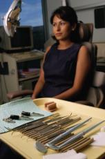 Fotografía de una paciente en la oficina del dentista con instrumentos dentales en una bandeja en primero plano