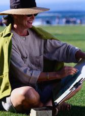 Fotografía de una mujer con sombrero y gafas de sol dibujando en el parque