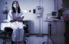 Photograph of a female patient in a hospital gown sitting in an exam room