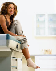 Photograph of a woman in an exam room with a sprained ankle