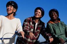 Fotografía de tres mujeres usando cascos de bicicleta
